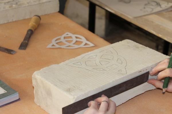 eleve de l atelier desculpture sur pierre qui dessine sur la pierre calcaire son motif a sculpter nantes renaissance